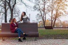 Adolescentes femeninos que escuchan la música en smartphone en el banco i Fotos de archivo libres de regalías