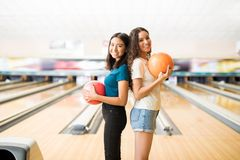 Adolescentes femeninos que sostienen bolas de bolos en club Imagen de archivo