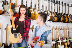 Adolescentes femeninos y masculinos atractivos que examinan las guitarras eléctricas Foto de archivo libre de regalías