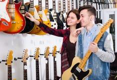 Adolescentes femeninos y masculinos que examinan las guitarras eléctricas Fotos de archivo libres de regalías