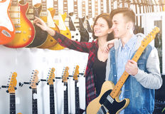 Adolescentes femeninos y masculinos que examinan las guitarras eléctricas Imagen de archivo