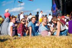 Adolescentes, festival de música del verano, sentándose delante de etapa Imagen de archivo