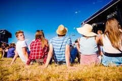 Adolescentes, festival de música del verano, sentándose delante de etapa Fotografía de archivo