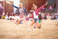 Adolescentes, festival de música, saltando, delante de etapa Fotos de archivo