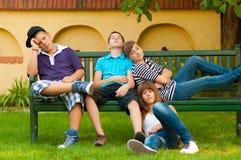 Adolescentes furados que sentam-se e que encontram-se no banco Fotografia de Stock Royalty Free