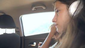 Adolescentes hermano y hermana en los auriculares que viajan junto en el coche, usando el teléfono almacen de metraje de vídeo
