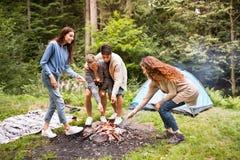 Adolescentes hermosos en bosque en la hoguera con las bengalas Foto de archivo libre de regalías