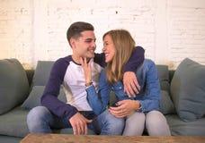 Adolescentes hermosos jovenes de los pares o novia 20s y novio románticos en el abrazo feliz sonriente del amor en el sofá casero Imagen de archivo libre de regalías