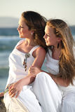 Adolescentes hermosos sobre el mar y el backgr de la puesta del sol Fotografía de archivo