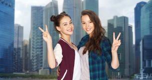 Adolescentes heureuses étreignant et montrant le signe de paix Photographie stock libre de droits