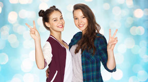 Adolescentes heureuses étreignant et montrant le signe de paix Images stock