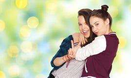 Adolescentes heureuses étreignant et montrant le signe de paix Image stock