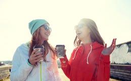 Adolescentes heureuses avec des tasses de café sur la rue Image libre de droits