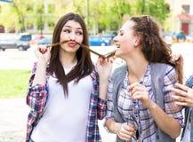 Adolescentes heureuses ayant l'amusement dans le parc ensoleillé d'été Temps chaud de ressort Images stock