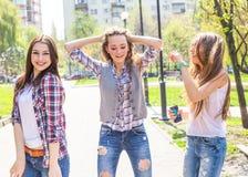Adolescentes heureuses ayant l'amusement dans le parc ensoleillé d'été Temps chaud de ressort Photos stock