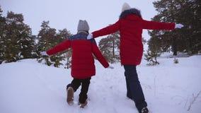 Adolescentes heureuses courant sur la route neigeuse, redressant leurs bras en vol Promenade en air frais des enfants dans le pin banque de vidéos