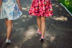 Adolescentes heureuses dans des robes légères marchant sur la lumière du soleil, dehors Amies méconnaissables ayant l'amusement e Photographie stock