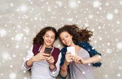 Adolescentes heureuses se trouvant sur le plancher avec le smartphone Photos stock