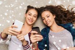 Adolescentes heureuses se trouvant sur le plancher avec le smartphone Images stock