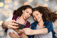 Adolescentes heureuses sur le plancher et le selfie de prise Images libres de droits