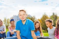Adolescentes internacionales que se sientan junto en parque Foto de archivo