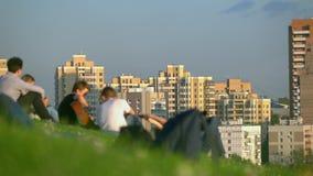Adolescentes irreconocibles que cuelgan hacia fuera en parque de la ciudad y que escuchan la guitarra contra urbanscape Fotografía de archivo