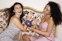 Adolescentes jouant avec les brosses et le sèche-cheveux Photos libres de droits