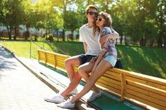 Adolescentes jovenes elegantes de los pares que se sientan en la ciudad del banco, día de verano Foto de archivo libre de regalías