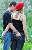 Adolescentes jovenes en vaqueros del dril de algodón del amor que llevan Foto de archivo libre de regalías