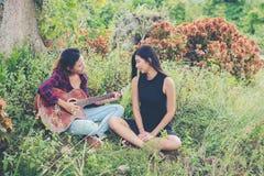 Adolescentes jovenes mirando a su amigo femenino mientras que tocan la guitarra, Fotos de archivo