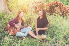 Adolescentes jovenes mirando a su amigo femenino mientras que tocan la guitarra, Imagen de archivo