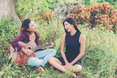 Adolescentes jovenes mirando a su amigo femenino mientras que tocan la guitarra, Fotos de archivo libres de regalías