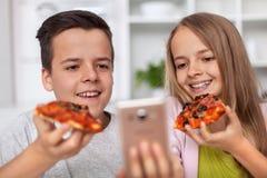 Adolescentes jovenes que comen rebanadas de la pizza y que toman un selfie fotos de archivo libres de regalías