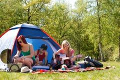 Adolescentes jovenes que tienen un rato agradable en acampar Fotografía de archivo
