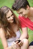 Adolescentes jovenes sonrientes que usan un móvil Fotos de archivo