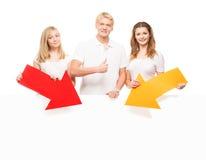 Adolescentes jovenes y felices que sostienen indicadores coloridos Fotos de archivo