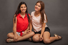 Adolescentes latinos bonitos que sentam-se para baixo Imagem de Stock Royalty Free