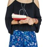 Adolescentes lindos con el auricular y sostener el libro rojo Foto de archivo libre de regalías