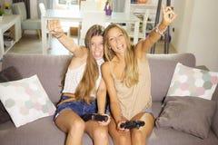 Adolescentes lindos que juegan el videojuego con la cámara de mirada sonriente feliz de la consola Imágenes de archivo libres de regalías