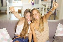 Adolescentes lindos que juegan el videojuego con el primer de mirada sonriente feliz de la cámara de la consola Fotografía de archivo libre de regalías