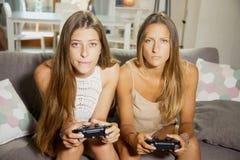 Adolescentes lindos que juegan el videojuego que sostiene la palanca de mando Foto de archivo