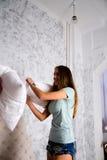 Adolescentes lindos que luchan con las almohadas en la cama Foto de archivo libre de regalías