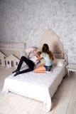 Adolescentes lindos que luchan con las almohadas en la cama Imágenes de archivo libres de regalías