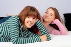 Adolescentes lindos que mienten en la cama y la sonrisa Foto de archivo libre de regalías