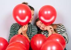 Adolescentes lindos que miran a escondidas detrás de los globos sonrientes Fotografía de archivo libre de regalías