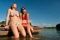 Adolescentes lindos que toman el sol en el barco Imagenes de archivo