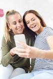 Adolescentes lisant le message textuel au téléphone portable photographie stock libre de droits