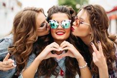 Adolescentes magníficos en gafas de sol que besan a su amigo que sonríe en la cámara con gesto del corazón Imagenes de archivo