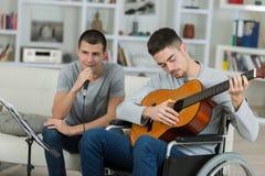 2 adolescentes masculinos que tocan la guitarra acústica y que cantan Imagen de archivo