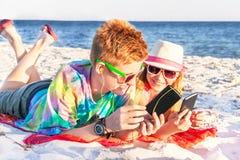 Adolescentes (menino e menina) que usam o telefone esperto e a música de escuta Fotos de Stock Royalty Free